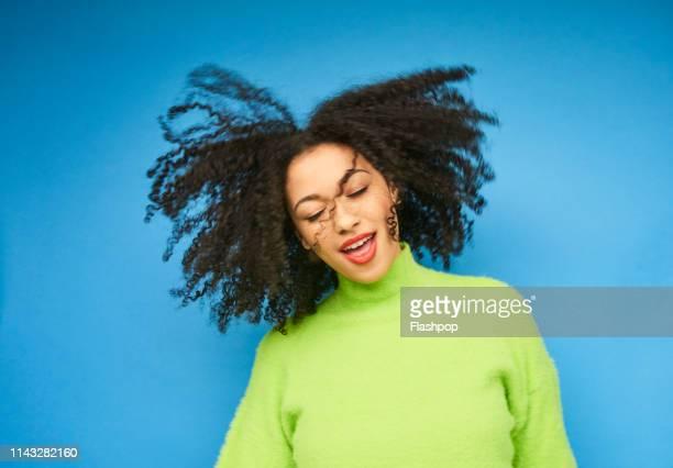 colourful studio portrait of a young woman dancing - solo una donna giovane foto e immagini stock