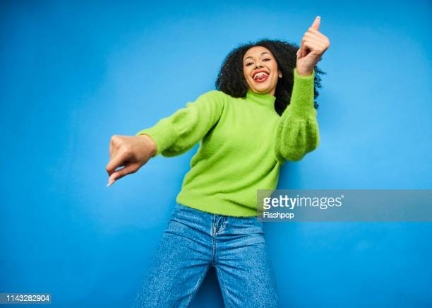 colourful studio portrait of a young woman dancing - tevreden stockfoto's en -beelden