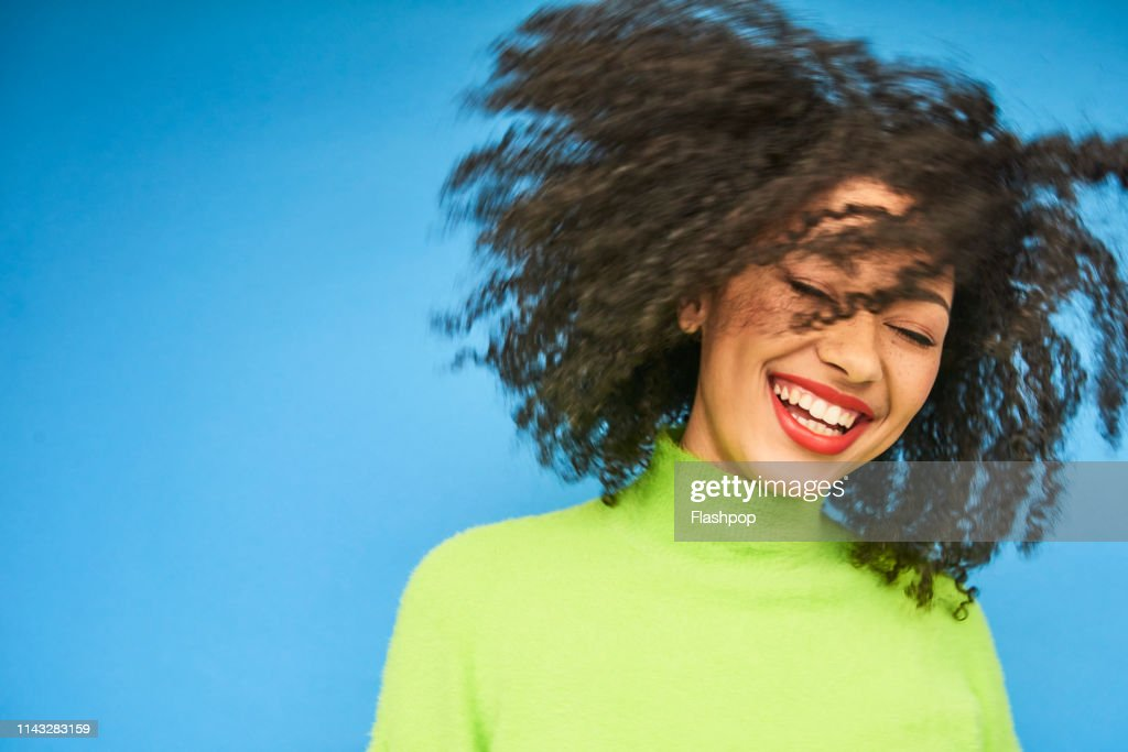 Colourful studio portrait of a young woman dancing : Stock Photo