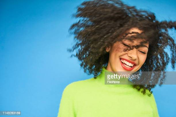 colourful studio portrait of a young woman dancing - insouciance photos et images de collection