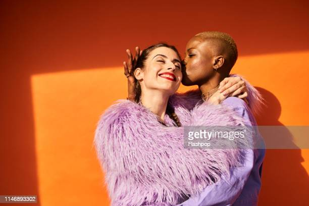 colourful studio portrait of two women - bonding stock pictures, royalty-free photos & images