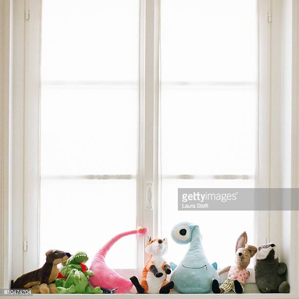 Colourful stuffed toys on windowsill