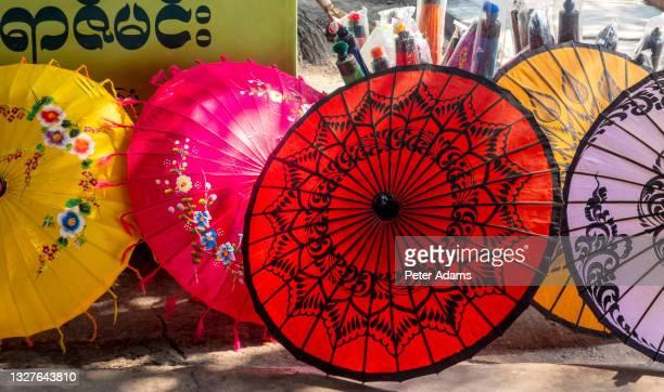 colourful sun parasols at street market in bagan, mandalay region, myanmar - peter adams stock pictures, royalty-free photos & images