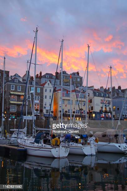 colourful sunset sky over st peter port waterfront, guernsey. - passenger craft stock pictures, royalty-free photos & images