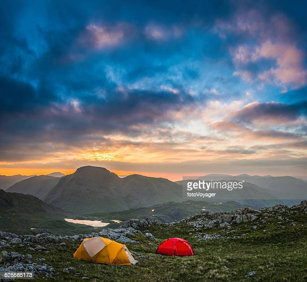 Colourful tents camping under idyllic mountain sunset Lake District UK