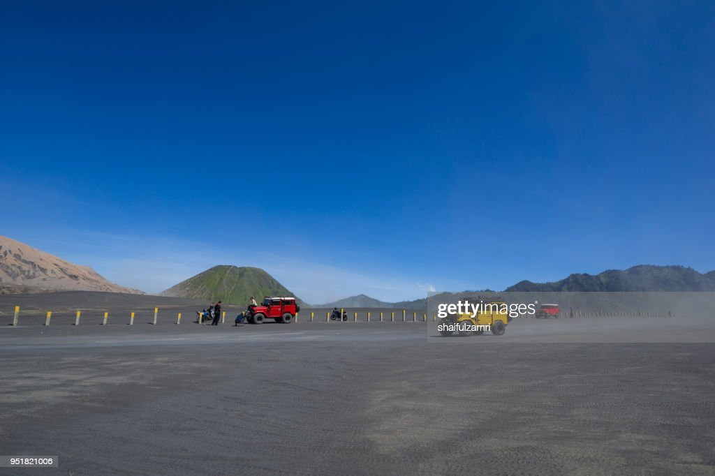 Colourful tourist jeeps in savanna of Tengger caldera at Mt. Bromo, East Java, Indonesia. : Stock Photo