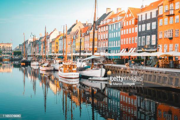 colourful townhouses facades and old ships along the nyhavn canal, copenhagen - copenhague photos et images de collection