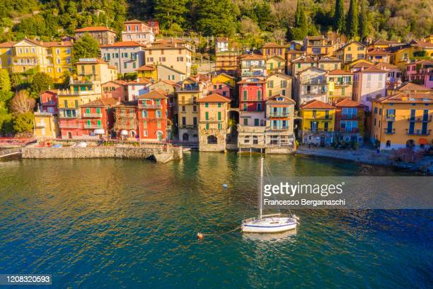 colourful traditional houses of varenna with a moored sailing boat. - chum stock-fotos und bilder