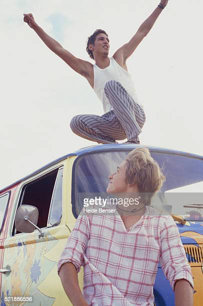 Colourful van, man squatting on top