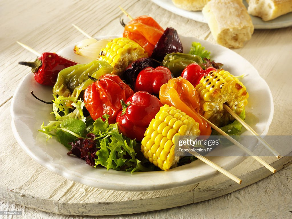 Colourful vegetable kebabs on salad leaves, close up : Stock Photo