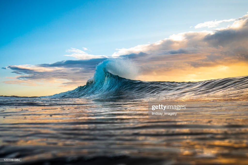 Colourful wave peaking into a flare with sunrise storm : Stock Photo