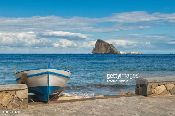 colourful wooden fishing boat with lisca bianca rock in the background - äolische inseln stock-fotos und bilder