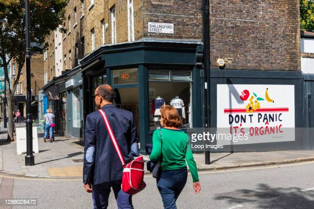 Colourfully dressed couple walk past boutique shops and a wall mural saying Don't Panic It's Organic on a street corner in Islington.