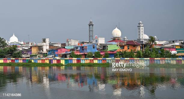 A colourfully painted barrier separates a waterway and a slum area in Jakarta on May 8 2019