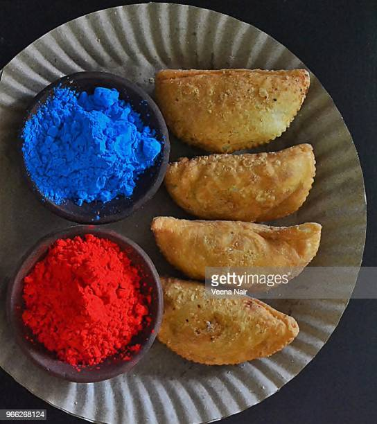 Colours of Holi and Gujiya/sweet dumpling  in a paper plate