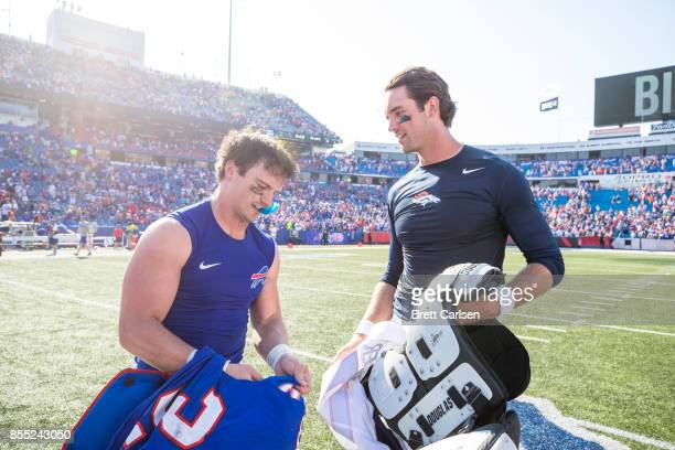 Colt Anderson of the Buffalo Bills and Brock Osweiler of the Denver Broncos trade jerseys after the game on September 24 2017 at New Era Field in...