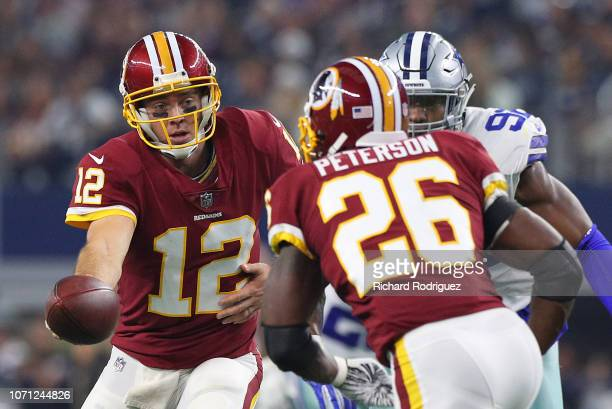 Colt McCoy hands the ball off to Adrian Peterson of the Washington Redskins in a football game at ATT Stadium on November 22 2018 in Arlington Texas