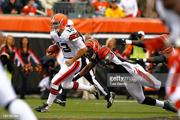 Colt McCoy of the Cleveland Browns runs from Michael Johnson of the Cincinnati Bengals at Paul Brown Stadium on November 27 2011 in Cincinnati Ohio