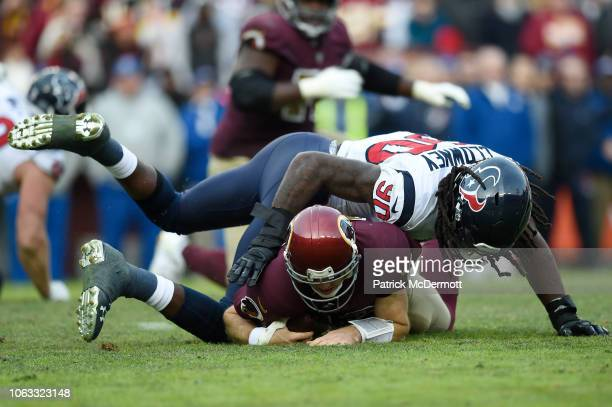 Colt McCoy of the Washington Redskins is tackled by Jadeveon Clowney of the Houston Texans in the fourth quarter at FedExField on November 18 2018 in...