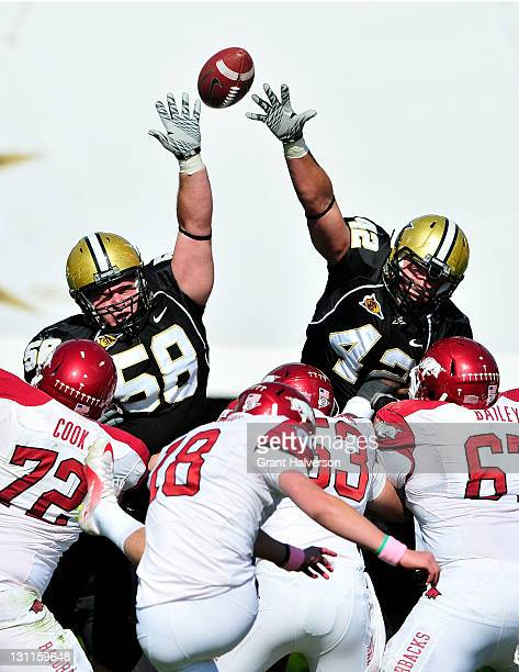 Colt Nichter and Tim Fugger of the Vanderbilt Commodores leap to block a field goal by Zach Hocker of the Arkansas Razorbacks during play at...