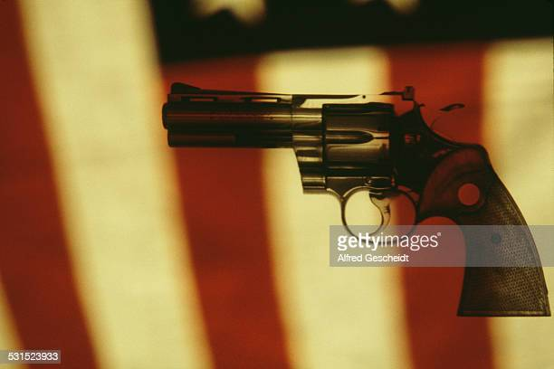 A Colt Python a 357 Magnum caliber revolver set against the background of an American flag 1982