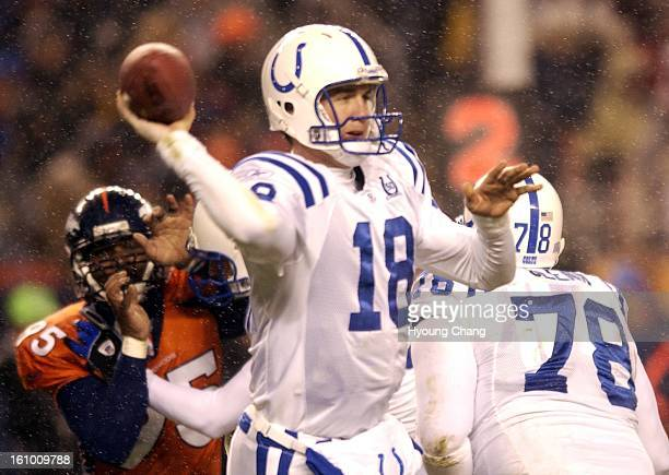 Colt Qb Peyton Manning gets of a pass as Bronco Kavika Pittman tries to get to him in the first half of the game at Invesco Field at Mile High on...