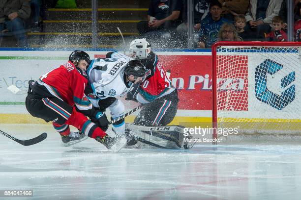 Colton Kroeker of the Kootenay Ice is checked between Gordie Ballhorn and Roman Basran of the Kelowna Rockets on December 2 2017 at Prospera Place in...