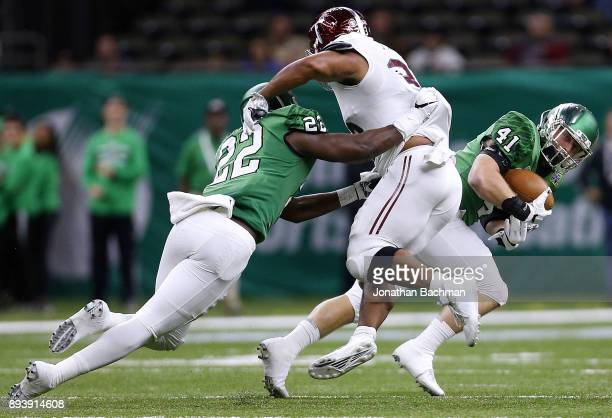 Colton McDonald of the North Texas Mean Green returns a fumble for a touchdown as EJ Ejiya blocks Josh Anderson of the Troy Trojans in the first half...