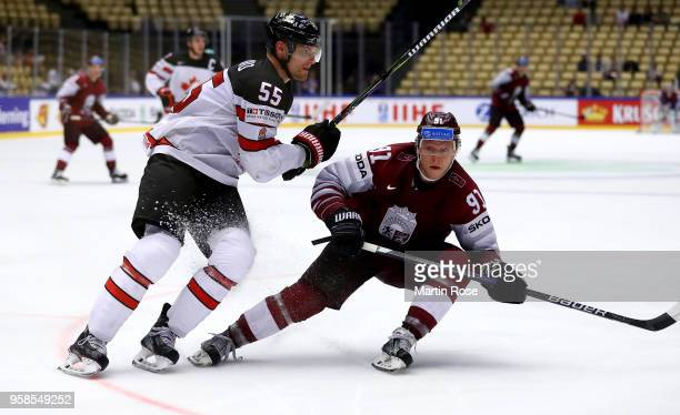 Colton Parayko of Canada skates against Ronalds Kenins of Latvia battle for the puck during the 2018 IIHF Ice Hockey World Championship Group B game...