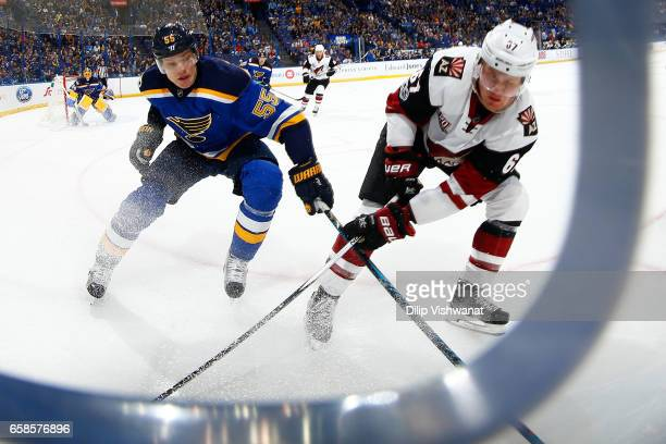 Colton Parayko of the St Louis Blues and Lawson Crouse of the Arizona Coyotes chase down the puck at the Scottrade Center on March 27 2017 in St...