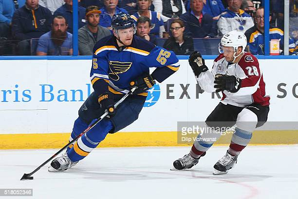Colton Parayko of the St Louis Blues controls the puck against the Andrew Agozzino of Colorado Avalanche at the Scottrade Center on March 29 2016 in...
