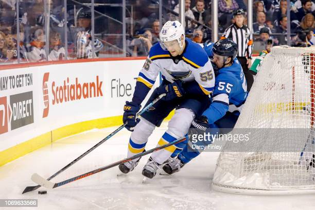 Colton Parayko of the St Louis Blues plays the puck around the net as Mark Scheifele of the Winnipeg Jets defends during second period action at the...