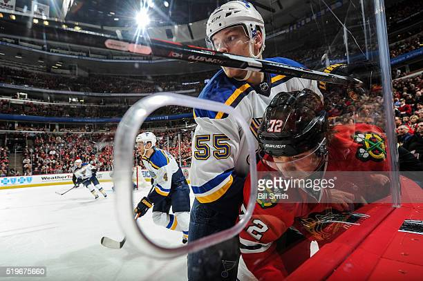 Colton Parayko of the St Louis Blues pushes Artemi Panarin of the Chicago Blackhawks into the boards in the first period of the NHL game at the...