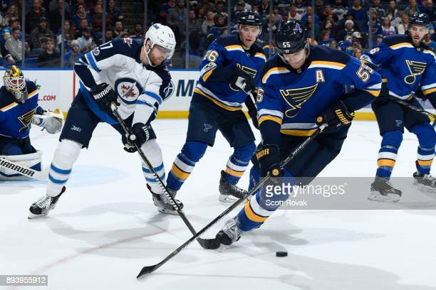 Colton Parayko of the St Louis Blues steals the puck from Adam Lowry of the Winnipeg Jets at Scottrade Center on December 16 2017 in St Louis Missouri