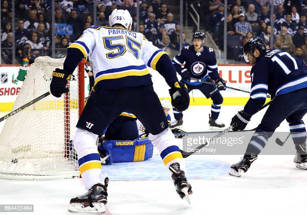 Colton Parayko of the St Louis Blues watches as Adam Lowry of the Winnipeg Jets deflects a puck into the net for a second period goal at the Bell MTS...