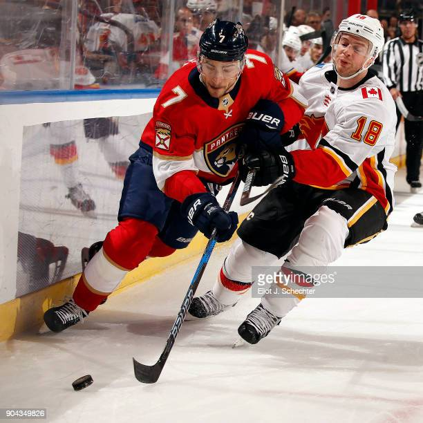 Colton Sceviour of the Florida Panthers skates for possession along the boards against Matt Stajan of the Calgary Flames at the BBT Center on January...