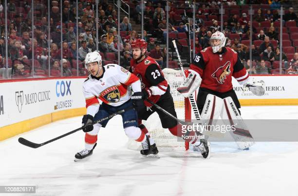 Colton Sceviour of the Florida Panthers skates to the loose puck while being defended by Oliver EkmanLarsson of the Arizona Coyotes as goalie Darcy...