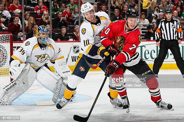 Colton Sissons of the Nashville Predators and Dennis Rasmussen of the Chicago Blackhawks wait in position in front of goalie Marek Mazanec in the...