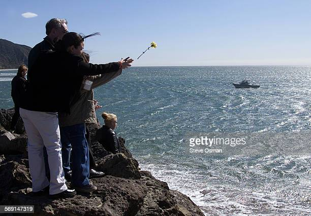 Columba Chavez Garcia left and her niece Candy Chavez throw a flower into the Pacific Ocean at Pt Mugu during a stone dedication ceremony Wednesday...