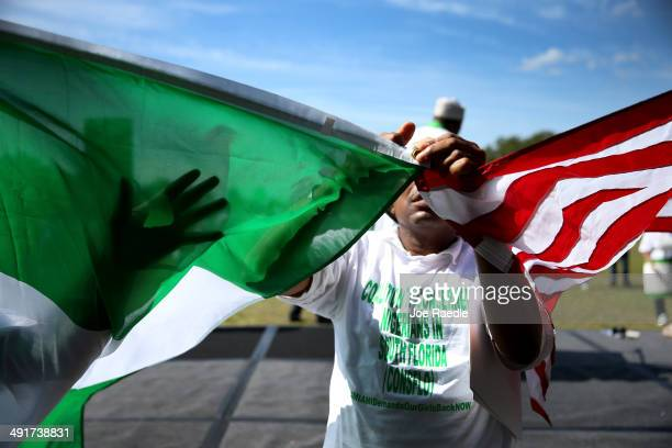 Columba chris Okpala joins an American flag and Nigerian flag together as he and others rally to support the Coalition of Concerned Nigerians in...