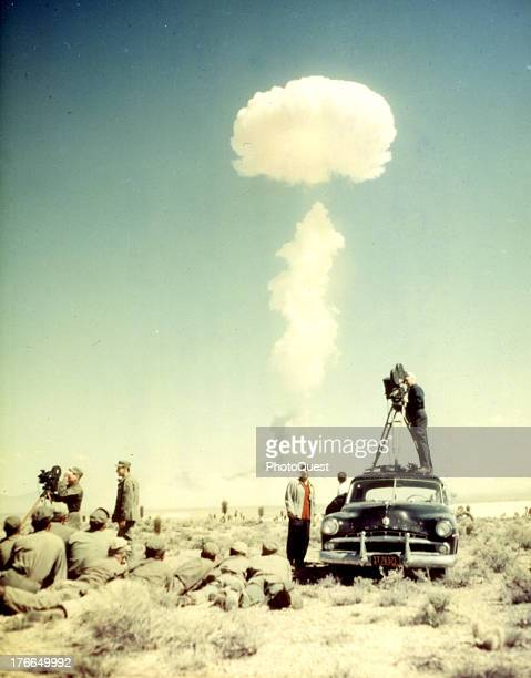 Columbia Broadcasting System TV newsreel cameraman and troops watching an atomic bomb test explosion Yucca Flats Nevada April 22 1952