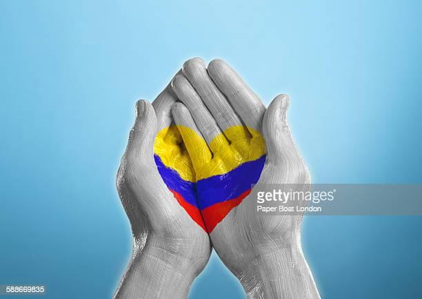 columbia heart shaped flag painted on a hand - bandera colombiana fotografías e imágenes de stock