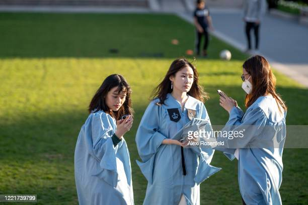 Columbia University student wearing a mask takes photos with her fellow students in their cap and gowns amid the coronavirus pandemic on April 28,...