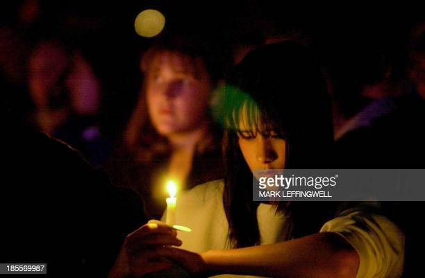 A Columbine student who wished to remain unidentified bows her head in prayer during late 20 April 2000 candle light vigil ending the one year...