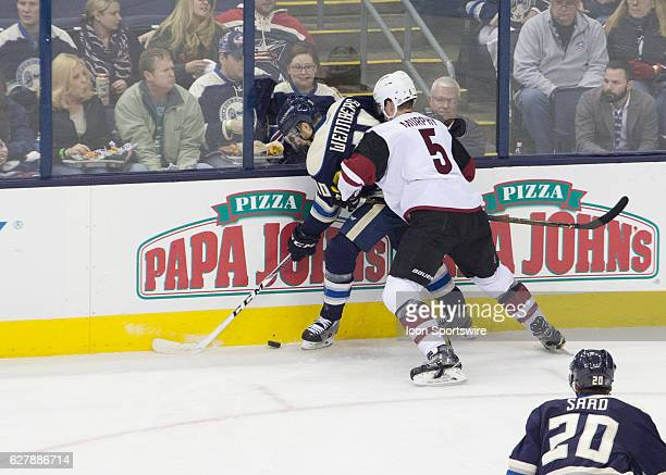 Columbus Blue Jackets center Alexander Wennberg and Arizona Coyotes defenseman Connor Murphy battle for the puck along the boards during the first...