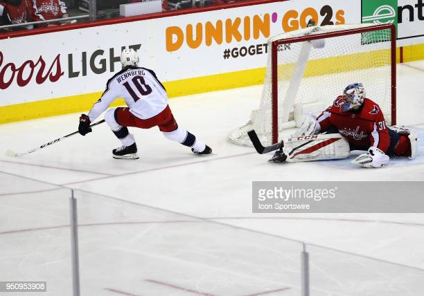 Columbus Blue Jackets center Alexander Wennberg slips the puck between the legs of Washington Capitals goaltender Philipp Grubauer for a goal during...