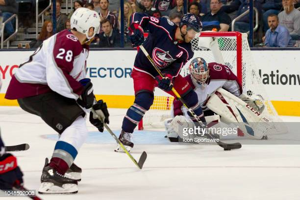 Columbus Blue Jackets center Boone Jenner attempts a shot as Colorado Avalanche goaltender Philipp Grubauer defends in the third period of a game...