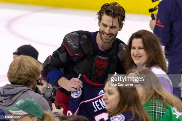 Columbus Blue Jackets center Boone Jenner poses with the winner of his gameworn jersey after winning a game between the Columbus Blue Jackets and the...