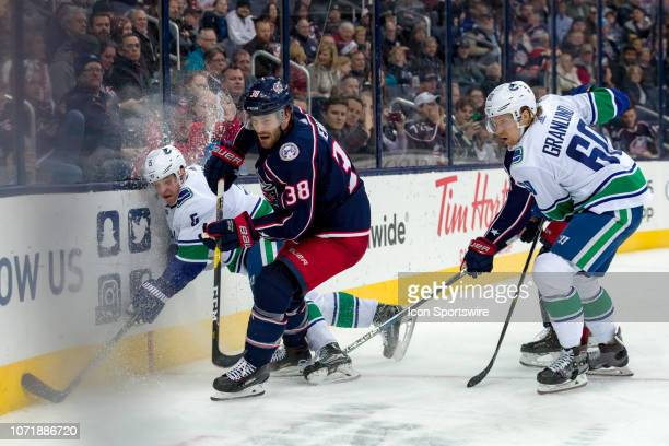 Columbus Blue Jackets center Boone Jenner slams Vancouver Canucks defenseman Derrick Pouliot into the board in a game between the Columbus Blue...