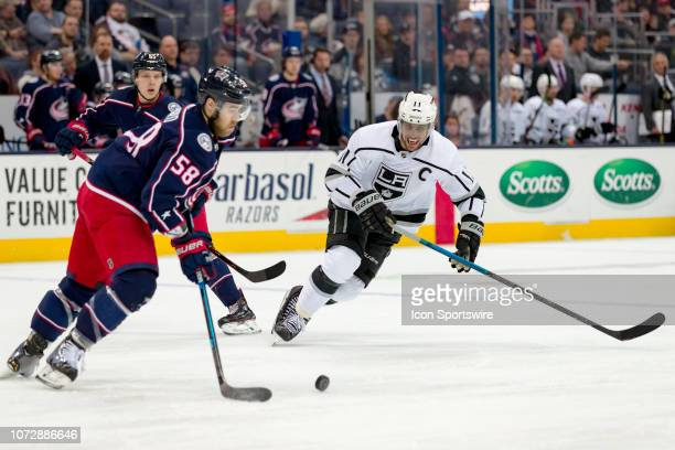 Columbus Blue Jackets defenseman David Savard controls the puck as Los Angeles Kings center Anze Kopitar pursues in a game between the Columbus Blue...